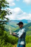 研究在山的膝上型计算机的年轻人 库存照片