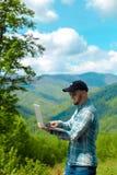 研究在山的膝上型计算机的年轻人 免版税库存图片