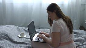 研究在床上的膝上型计算机的无忧无虑的妇女 股票视频
