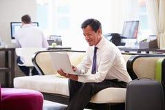 研究在旅馆大厅的膝上型计算机的商人 免版税库存照片