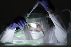 研究在生物危险实验室的生活科学家 高度保护工作 免版税库存照片