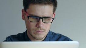 研究在白色背景的膝上型计算机的镜片的人 影视素材