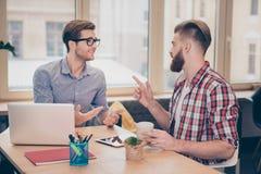 研究在网上项目的两位年轻自由职业者计划谈话的最好的朋友有交谈在看彼此的咖啡馆gestu 免版税图库摄影