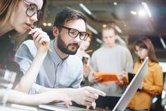 研究在膝上型计算机的一个新的项目的企业队 关于一个新的工作计划的讨论 免版税库存照片