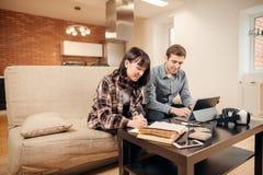 研究在膝上型计算机的一个项目的两名学生,大气是舒适和温暖的 免版税库存照片