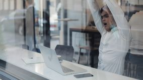研究在舒适咖啡馆的膝上型计算机和打呵欠在白天的疲乏的商人 股票视频