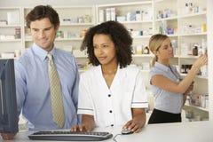 研究在药房的计算机的护士 免版税库存图片