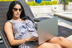 研究在近的游泳池之外的膝上型计算机的西班牙妇女 库存照片