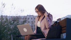 研究在长凳的膝上型计算机的美丽的被集中的自由职业者在城市公园 股票视频