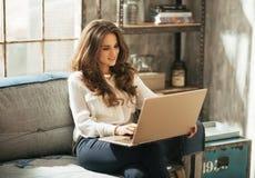 研究在顶楼公寓的膝上型计算机的少妇 免版税库存照片