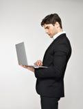研究在黑色诉讼的膝上型计算机的生意人 免版税图库摄影
