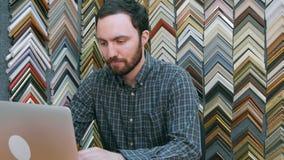 研究在他的商店后柜台的膝上型计算机的一个年轻男性企业主的画象  库存图片