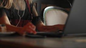 研究她的在一家时髦的都市餐馆的膝上型计算机的美丽的妇女 股票录像