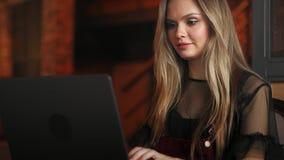 研究她的在一家时髦的都市餐馆的膝上型计算机的美丽的妇女 股票视频
