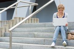 研究她的膝上型计算机的十几岁的女孩 免版税库存照片