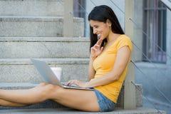 研究她的膝上型计算机的可爱的拉丁妇女 免版税库存照片