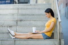 研究她的膝上型计算机的可爱的拉丁妇女 免版税库存图片