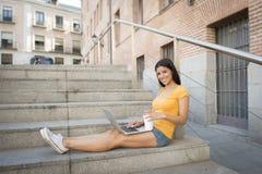 研究她的膝上型计算机的可爱的拉丁妇女 库存照片