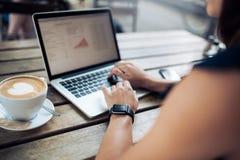 研究她的膝上型计算机的咖啡馆的妇女 免版税库存图片