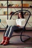 研究她的膝上型计算机的女孩,当坐一把舒适的椅子时 库存图片