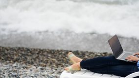 研究她的膝上型计算机的妇女在海附近 股票录像