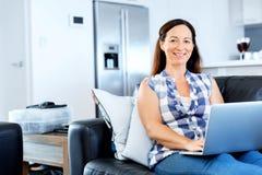 研究她的膝上型计算机的成熟美丽的妇女 免版税图库摄影