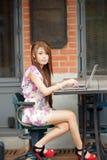 研究她的膝上型计算机的新可爱的女商人在室外 免版税库存图片