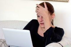 研究她的膝上型计算机的沮丧的妇女 库存图片