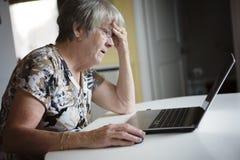 研究她的膝上型计算机的资深妇女在她的厨房里 库存照片