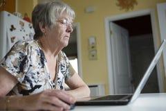 研究她的膝上型计算机的资深妇女在她的厨房里 图库摄影