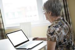 研究她的膝上型计算机的资深妇女在她的厨房里 库存图片