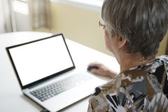 研究她的膝上型计算机的资深妇女在她的厨房里 免版税库存照片