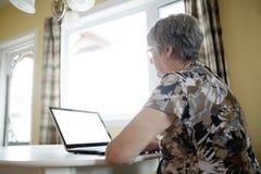 研究她的膝上型计算机的资深妇女在她的厨房里 免版税图库摄影