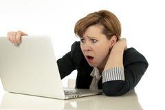 研究她的计算机的可爱的年轻女商人被注重,担心和被淹没 免版税库存图片