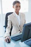 研究她的计算机的快乐的可爱的女实业家 免版税库存图片
