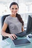研究她的计算机的快乐的女实业家 免版税库存图片