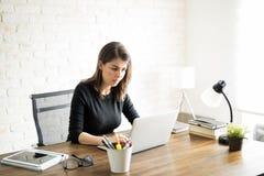 研究她的计算机的拉丁妇女 免版税库存图片