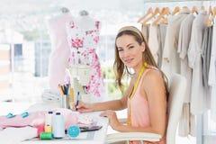研究她的设计的一位女性时装设计师的画象 库存照片