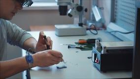 研究实验室,机器人学工程师检查微集成电路的操作在一个移动设备的 股票视频