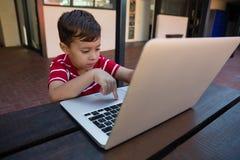 研究数字式膝上型计算机的逗人喜爱的男孩,当坐在桌上时 图库摄影