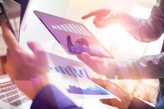 研究新的全球性财政战略的两个同事计划使用片剂和膝上型计算机 现代企业队创新 免版税库存图片