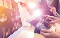 研究新的全球性财政战略的两个同事计划使用片剂和膝上型计算机 现代企业队创新 图库摄影
