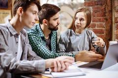 研究新的项目的小组偶然商人 他们使用膝上型计算机和谈论关于概念 解决问题 库存图片