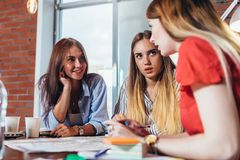 研究新的项目的小组女性工友坐在书桌在创造性的办公室 免版税库存照片