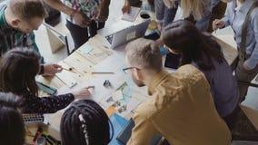 研究新的项目的年轻队顶视图 小组站立在桌和谈论附近的混合的族种人 库存照片