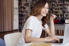 研究有书的膝上型计算机的年轻女实业家企业家或大学生在科学论文在图书馆里,微笑 免版税库存图片