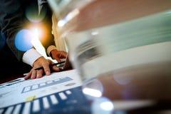 研究有企业图表的便携式计算机的商人手 免版税库存照片