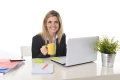 研究有咖啡杯的计算机膝上型计算机的愉快的白肤金发的女商人 库存照片