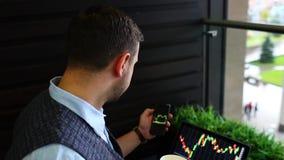 研究有图的膝上型计算机的自由职业者商人在咖啡馆的屏幕上,检查智能手机应用信息 影视素材