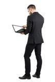 研究有空白的空的屏幕的一台膝上型计算机的商人背面图 库存照片